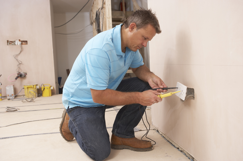 Professional electrician working on an outlet