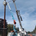 Electricians tearing down an old traffic signal at Lake Slough.