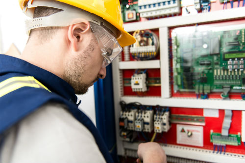 An electrician working on an industrial electric project in Portland OR
